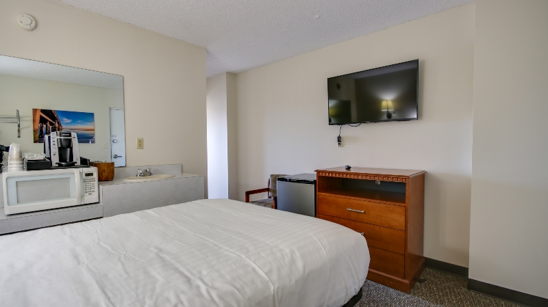 queen bed with dresser tv and microwave